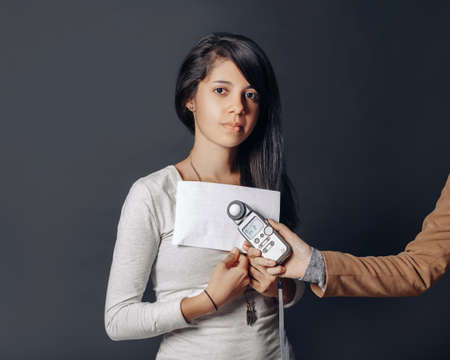 Portrait of beautiful hispanic latin brunette young woman in studio holding white paper and flash meter, measuring light, on plain black background