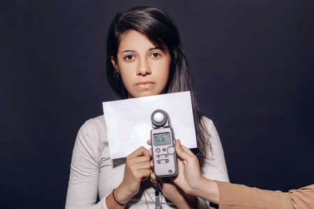 shutter aperture: Portrait of beautiful hispanic latin brunette young woman in studio holding white paper and flash meter, measuring light, on plain black background