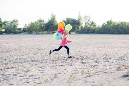 Portrait of white Caucasian teenager child girl with colorful bunch of balloons running on sand beach on sunset outdoors looking away,  happy lifestyle childhood concept