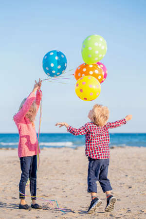 Retrato de grupo de dos divertidos niños caucásicos blancos niños con colorido montón de globos jugando corriendo en la playa en la puesta de sol, concepto de la niñez de vida feliz