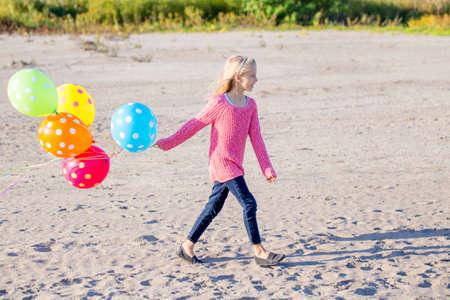 Retrato de niña de raza caucásica blanca del adolescente con el montón colorido de globos que se ejecutan en la playa de arena en la puesta del sol al aire libre mirando a otro lado, concepto de la niñez de estilo de vida feliz