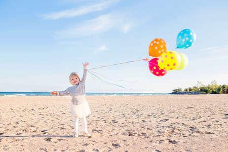 Retrato de la niña linda divertido blanco del cabrito del niño caucásico con el manojo colorido de globos, jugando sonriendo en la playa en puesta del sol, concepto feliz de la niñez del estilo de vida
