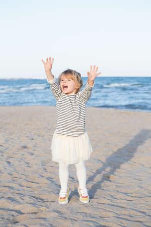 Retrato de un divertido llorando gritando saltando arriba Blanco niño de raza caucásica niña en camisa a rayas y tutú falda, en el mar del océano playa al atardecer al aire libre, concepto de la niñez de vida feliz Foto de archivo