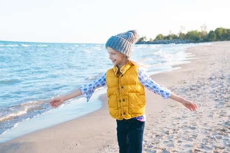 Retrato de sonriente rubia chica de raza caucásica blanco niño con pelo largo vistiendo chaqueta amarilla chaleco y sombrero gris, en la orilla del mar playa de arena al atardecer mirando a otro lado, estilo de vida feliz de la niñez