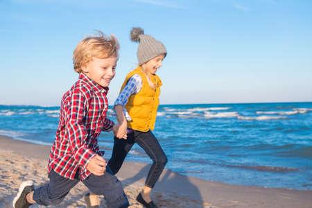 Retrato de grupo de dos divertidos niños caucásicos blancos amigos de los niños corriendo en la playa de mar del océano al atardecer, el concepto de la niñez de vida feliz