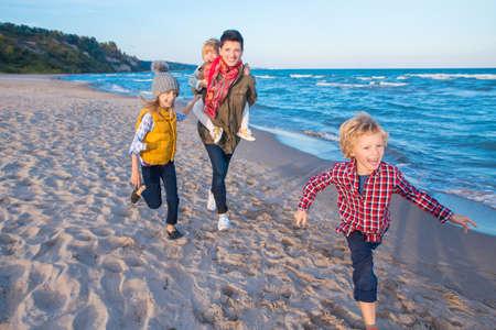 Retrato de grupo de tres divertidos sonriente riendo niños blancos de raza caucásica niños con la madre corriendo en la playa de mar del océano al atardecer al aire libre, concepto de la niñez de vida feliz