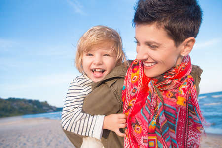 Retrato de grupo de sonriente de raza caucásica blanca madre e hija niña, piggyback montar, jugando corriendo en el océano mar playa al atardecer al aire libre, feliz concepto de la infancia de la vida