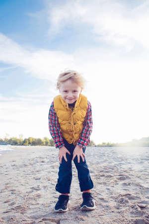 Retrato de divertida sonriente riendo blanco Niño caucásico niño rubio de pie en la playa de arena al atardecer buscando en la cámara, el concepto de la niñez feliz estilo de vida Foto de archivo