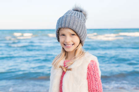 Portrait of smiling blonde white Caucasian child kid girl with long hair wearing white fur jacket gilet and grey hat, on sea shore beach looking in camera, happy lifestyle childhood Stock Photo