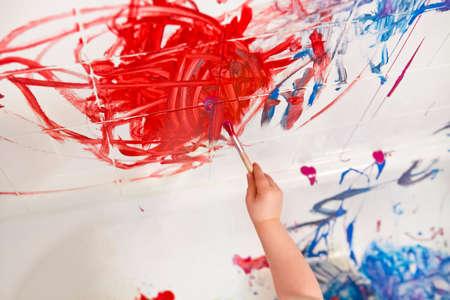 Primer plano de la mano del bebé brazo sosteniendo cepillo de pintura en la pared en la bañera de baño con pintura roja brillante, el desarrollo de la educación temprana, el concepto de la niñez activa, el efecto de desenfoque de movimiento Foto de archivo