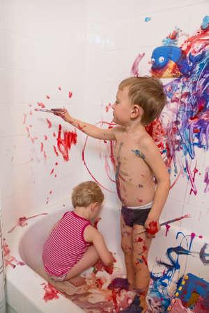 Retrato de dos lindos adorable blanco de raza caucásica niña y niña jugando pintura en las paredes en el baño, se divierten, estilo de vida activa concepto de la infancia, el desarrollo de la educación temprana