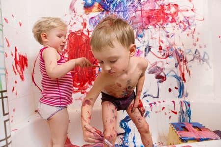 Portrait de deux mignons adorable blanc caucasien petit garçon et fille jouant à la peinture sur les murs dans la salle de bain, s'amuser, mode de vie concept d'enfance active, développement de l'éducation précoce