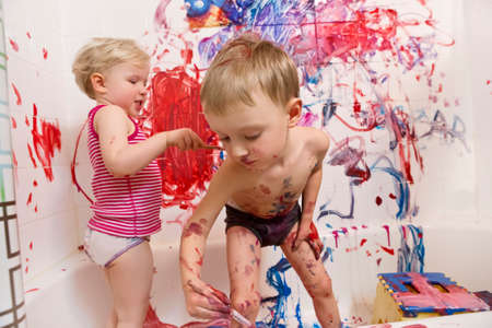 Portrait of two cute adorable white Caucasian little boy and girl playing painting on walls  in bathroom, having fun, lifestyle active childhood concept, early education development Stockfoto
