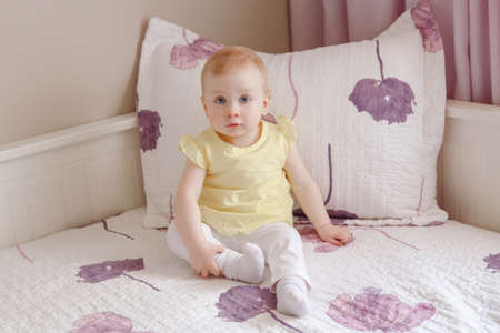 Portrait of cute adorable white blonde Caucasian smiling baby girl with large blue eyes in yellow shirt, sitting on bed, looking in camera