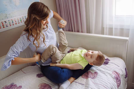 Funny group portrait of beautiful young white Caucasian mother and toddler child boy, playing together on bed in bedroom, having fun, natural candid family lifestyle Foto de archivo
