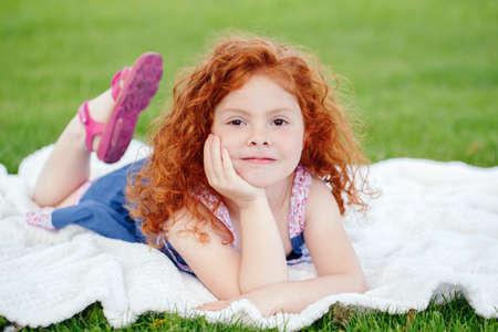 Portret van schattige schattige nadenkend klein roodharig Kaukasisch meisjeskind in blauwe jurk liggend op groen gras in park buiten, dromen denken, gelukkig levensstijl jeugdconcept Stockfoto