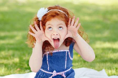 Portrait von niedlichen adorable kleine rothaarige kaukasischen Mädchen Kind im blauen Kleid machen lustige dumme Gesichter zeigen Zunge, im Park draußen, spielen weinen schreien, Spaß haben, Lebensstil Kindheit Standard-Bild