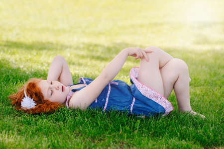 Portrait of cute adorable little red-haired Caucasian girl child in blue dress lying on grass in park outside looking up in sky, happy lifestyle childhood concept Stock Photo