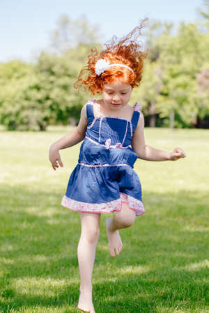 carroty: Portrait of cute adorable little red-haired Caucasian girl child in blue dress  jumping on grass in meadow park outside, funny candid moment, happy lifestyle childhood concept Stock Photo