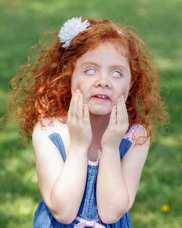 Portrait of cute adorable little red-haired Caucasian girl child in blue dress making funny scary silly faces in park outside, child rolling eyes, having fun, lifestyle childhood concept Stock Photo