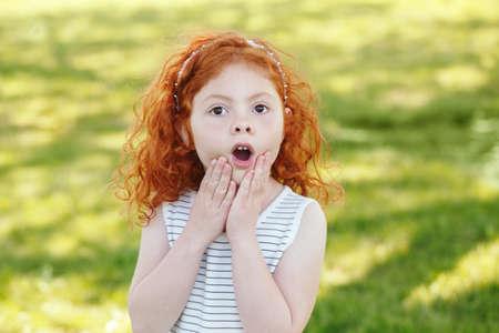 Portret van schattige aanbiddelijke verrast weinig roodharige Kaukasische meisje kind in gestreepte jurk in park buiten, spelen huilen schreeuwen in angst, gelukkige levensstijl jeugd concept Stockfoto