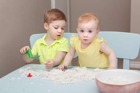 Group portrait of two cute siblings children playing kinetic sand or playdough together in kindergarden. Early creativity brain development concept. Lifestyle kids home activity.