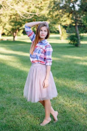 Porträt der schönen jungen kaukasischen Frau mit dem langen roten Haar im karierten Hemd und im rosa Ballettröckchen Tüllrock, barfuß stehend auf den Zehen auf Gras in der Parkwiese bei Sommersonnenuntergang stehend und weg schauen Standard-Bild - 81836174