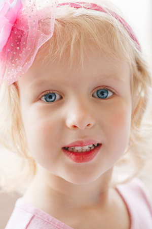 daily life: Closeup portrait of cute adorable blonde white Caucasian smiling baby girl with large blue eyes wearing pink headband, looking in camera