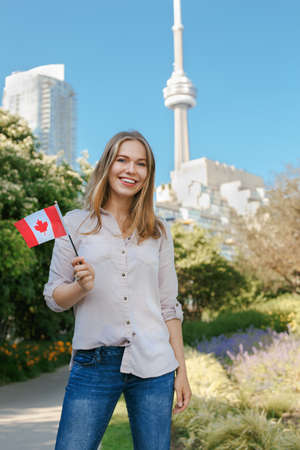 Portrait of beautiful smiling white blonde Caucasian woman holding waving Canadian flag with red maple leaf, outside in Toronto city near CN Tower, looking in camera, celebrating Canada Day