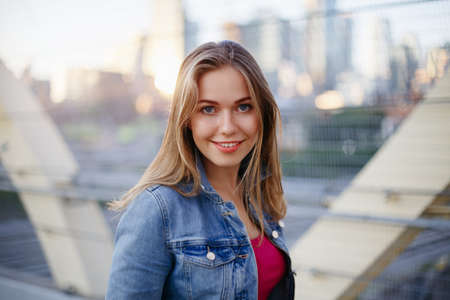 Portrait of beautiful smiling white Caucasian girl woman with long blonde  hair, wearing jeans jacket  outside in evening night city street bridge, looking in camera, lifestyle portrait concept