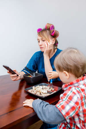 Bored tired white Caucasian young woman mother housewife with hair-curlers in hair looking on phone surfing Internet. Child son boy sitting eating meal lunch. Lifestyle concept. Stock Photo