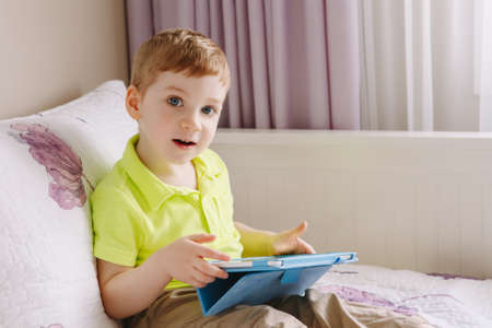 Portrait of cute adorable white Caucasian toddler boy sitting in bed playing with digital tablet looking in camera with funny face expression. Lifestyle early development. New technology generation.