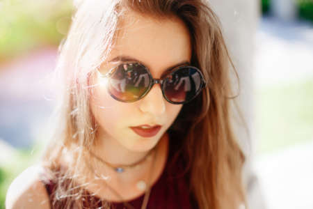 Closeup portrait of beautiful sexy pensive white Caucasian girl woman with long blond red hair, in sunglasses. Hot summer day, lifestyle concept. Sunny day outside, sunbeam leak lighting.