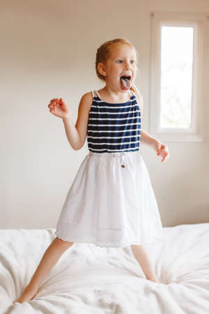 Portrait of cute finny white Caucasian blonde girl jumping on bed at home and showing tongue. Hilarious active kid having fun indoors. Authentic lifestyle childhood concept.