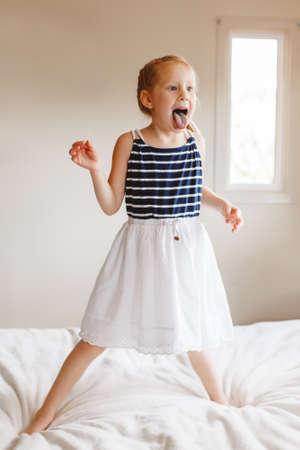 Portret van leuk finny wit Kaukasisch blondemeisje die op bed thuis springen en tong tonen. Hilarisch actief kind dat pret binnen heeft. Authentieke levensstijl jeugd concept. Stockfoto