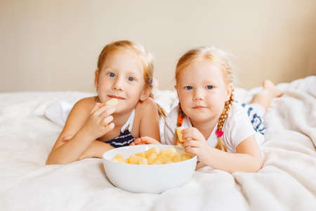 Portrait of two white Caucasian children girls eating corn puffs. Sisters eating snack fast food in bed at home indoors. Healthy meal childhood concept.