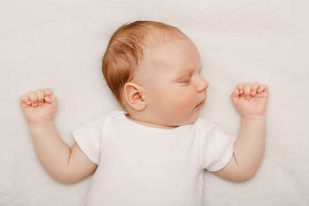 Portrait of sleeping cute Caucasian little baby newborn in white clothes lying on bed with his hands up. Lifestyle candid real concept. Stockfoto