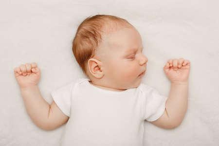 Retrato de dormir bebê caucasiano bonito recém nascido com roupas brancas deitada na cama com as mãos para cima. Conceito real sincero do estilo de vida.
