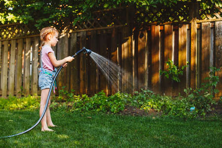Portrait of girl watering plants vegetables with gardening house on backyard on summer day. Child playing with water outside. Lifestyle family activity. Kids responsibility for doing home chores. Archivio Fotografico