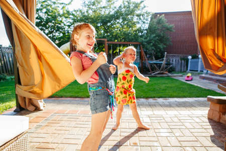 pretending: Portrait of  two little girls  sisters having fun on home backyard. Friends girls making silly faces. Lifestyle family moment of siblings playing together. Real authentic moment. Stock Photo