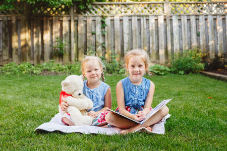 sitting on the ground: Group portrait of of two cute white Caucasian children friends sitting on grass outside with book. Preschool girls sisters reading book on backyard. Back to school fall concept.