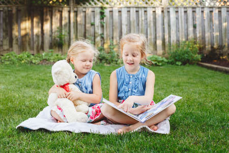 Group portrait of of two cute white Caucasian children friends sitting on grass outside with book. Preschool girls sisters reading book on backyard. Back to school fall concept.