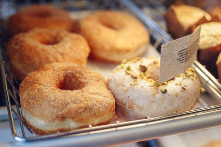 Coffee shop window with baked food, pastries. Closeup macro group of many round fresh organic doughnuts in basket with white paper Stock Photo