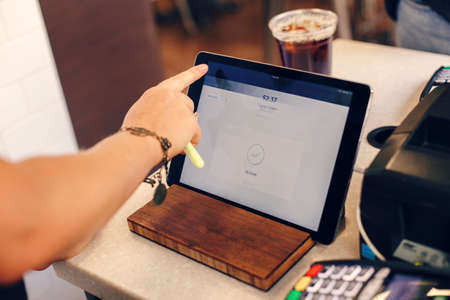 Closeup shot of young caucasian female woman cashier hands. Seller using touch pad for accepting client customer payment. Small business of coffee shop cafeteria. Archivio Fotografico