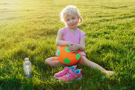 Portrait of happy cute adorable white Caucasian girl holding soft soccer ball. Child sitting in grass outside after playing soccer football game on summer day. Healthy lifestyle childhood concept. Stock Photo