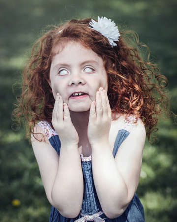 Portrait of cute adorable little red-haired Caucasian girl in blue dress making funny scary silly faces in park outside. Child rolling eyes, having fun, lifestyle Halloween concept.