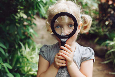 conservatory: Portrait of cute adorable white Caucasian girl looking in camera through flowers through magnifying glass. Child with loupe studying learning nature. Early development education concept.