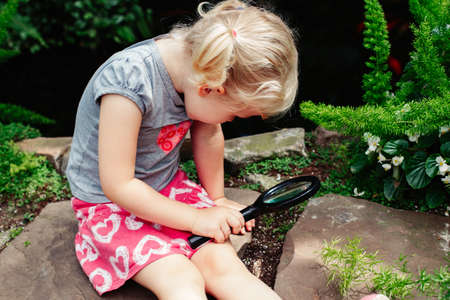 Portrait of cute adorable white Caucasian girl looking at plants grass through magnifying glass. Child with loupe studying learning nature. Early development education concept.