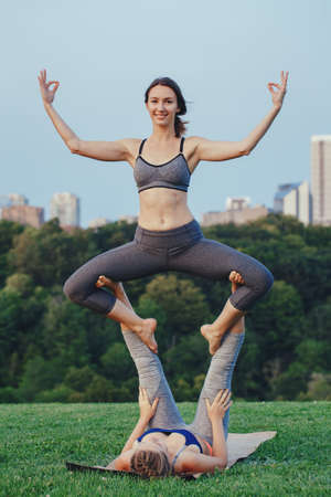 Two young beautiful Caucasian women yogi doing straddle throne acro yoga pose. Women doing stretching workout in park outdoors at sunset. Healthy lifestyle modern activity