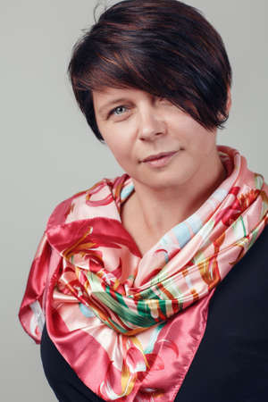 Closeup portrait of beautiful smiling middle aged white caucasian brunette woman with blue eyes covered with silk cotton scarf on her neck shoulders, looking in camera, on light background in studio